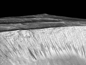 Listras escuras e estreitas visíveis nas paredes da cratera Garni, em Marte.