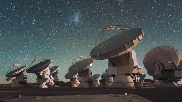 O Atacama Large Millimeter/submillimeter Array (ALMA) à noite, sob as Nuvens de Magalhães.
