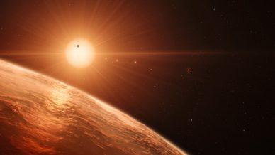 Imagem artística de uma estrela anã vermelha, com planetas a orbitar.