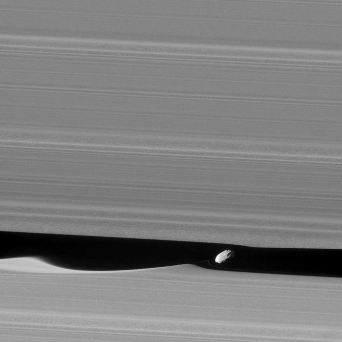 Dafnis, lua de Saturno, em órbita ao longo de um intervalo na parte exterior dos anéis deste planeta. Imagem obtida pela sonda Cassini em 2017.